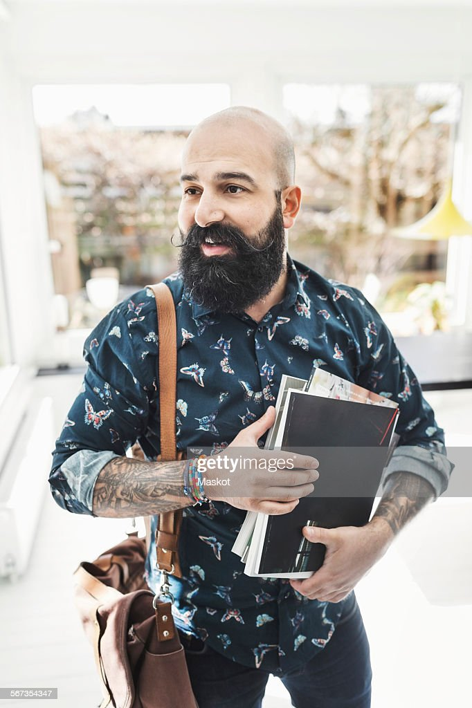 Male architect looking away while holding books at home