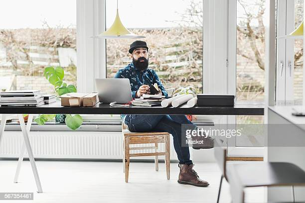 Male architect sitting at table by window