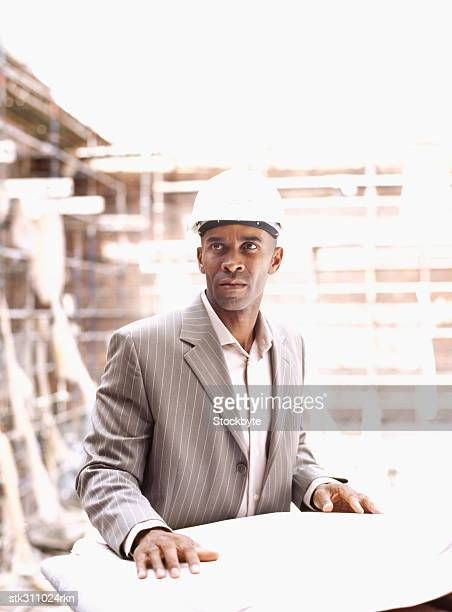male architect standing with a blueprint