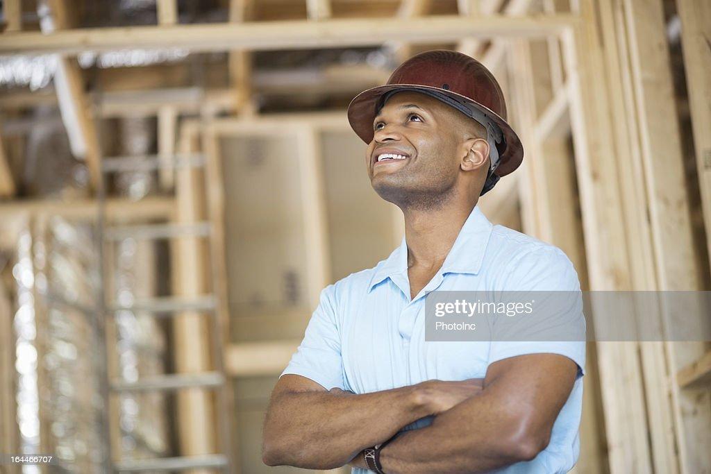 Male Architect Wearing Hardhat Examining Construction Site : Stock Photo