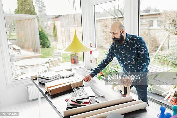 Male architect working at table in home office by window