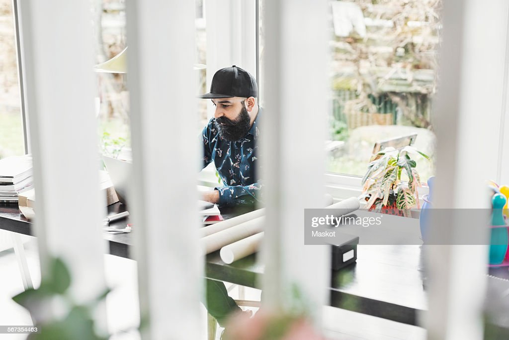 Male architect working at table in home office