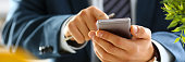 Male arm in suit hold phone and silver pen at workplace closeup. Read news mania send sms chat addict use electronic bank modern lifestyle job plan colleague share blog tweet web application search