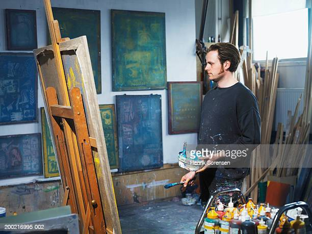 Male artist holding paint brush looking at canvas on easel in studio