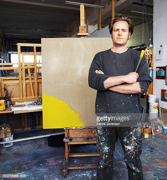 Male artist standing by canvas on easel, arms crossed, portrait