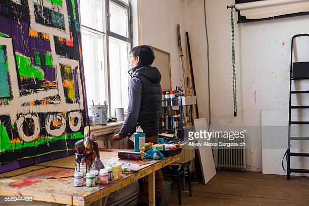 Male artist staring out of studio window