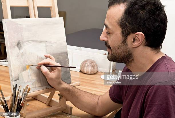Male artist working on abstract painting on small easel