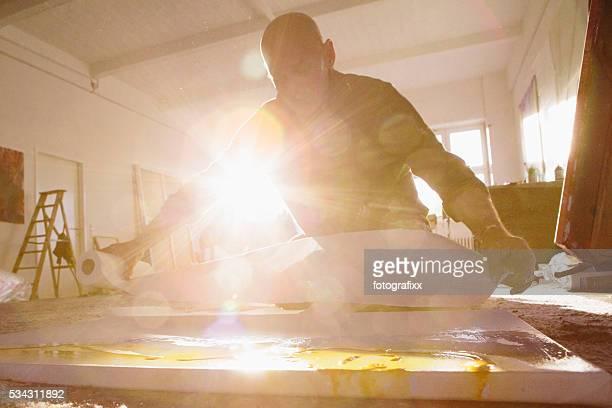 Maschio artista che lavora sulla sua dipinto nel suo studio,