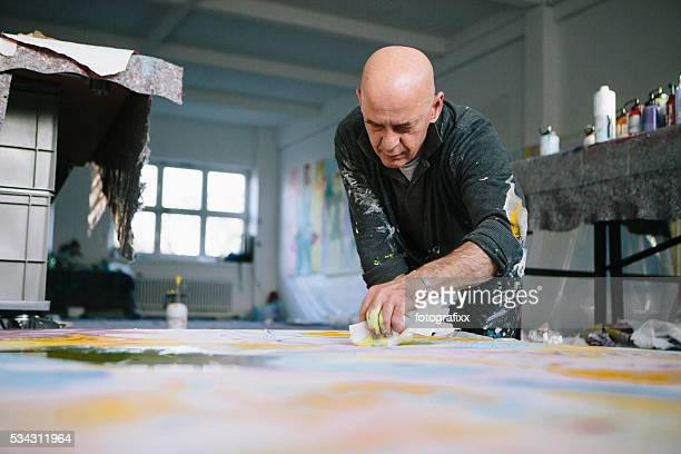 Male Artist works on his painting in his studio