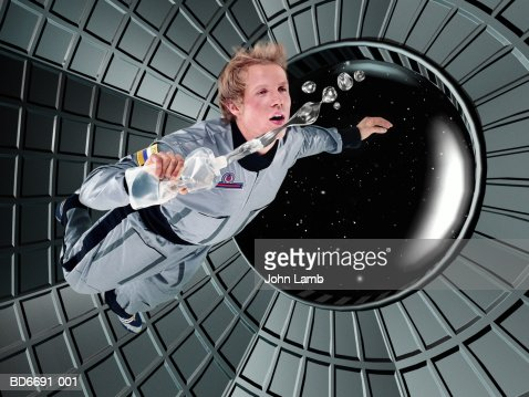 Male astronaut floating in space station (Digital Composite)
