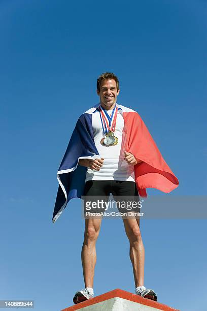 Male athlete being honored on podium, wrapped in French flag