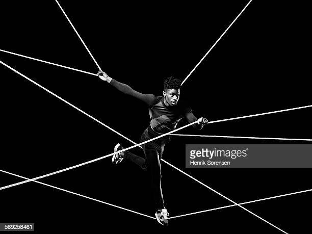 Male athlete blancing on ropes