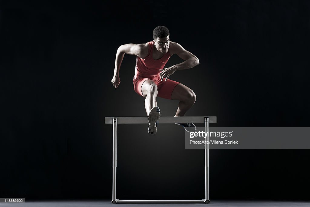 Male athlete clearing hurdle