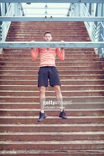 Male athlete doing exercise outdoor in urban enviroment