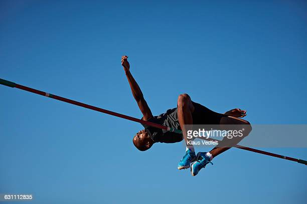 Male athlete doing high jump at sunset