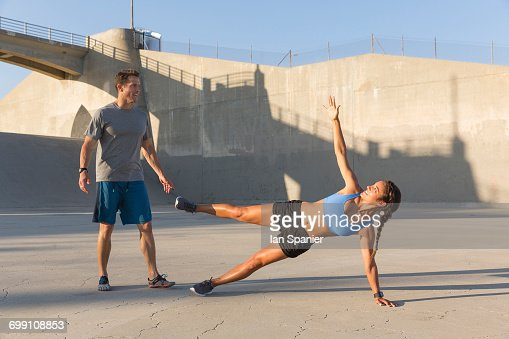 'Male athlete helping friend with workout, Van Nuys, California, USA'