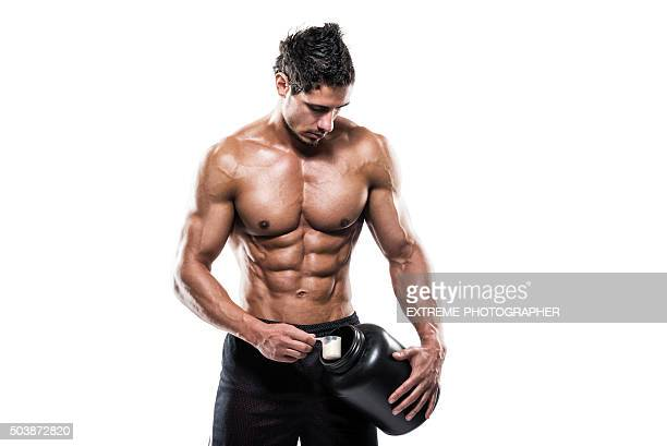 Male athlete holding bottle with supplement powder