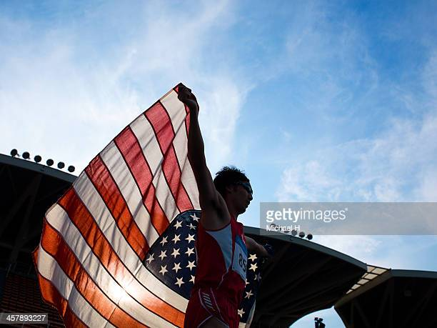 male athlete holding up American flag