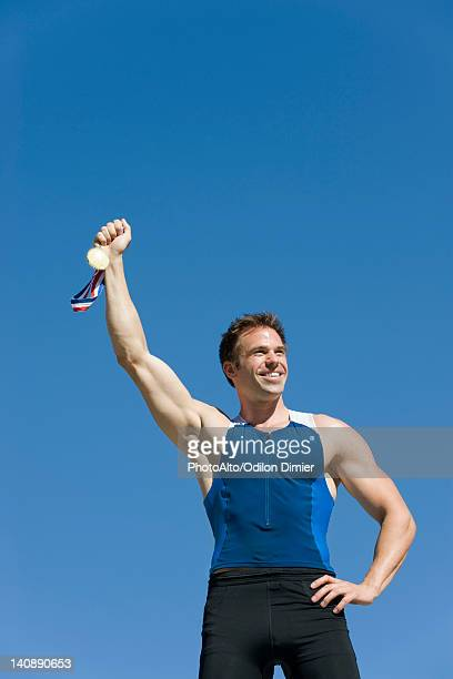 Male athlete holding up gold medal