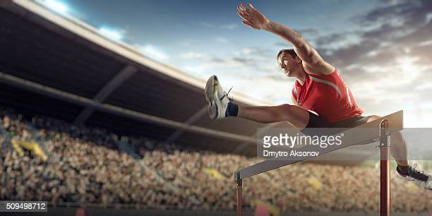 Male athlete hurdling on sports race