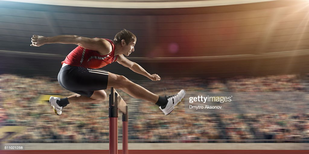 Male athlete hurdling on sports race : Stock Photo