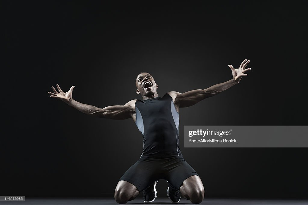Male athlete kneeling and shouting with despair : Stock Photo