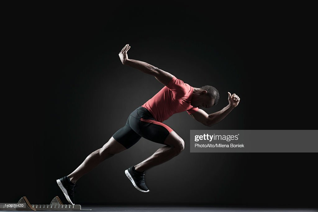 Male athlete leaving starting block