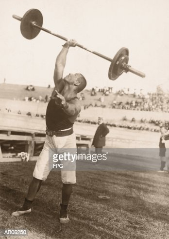 Male athlete lifting barbell on atletic field (B&W sepia tone) : Stock Photo