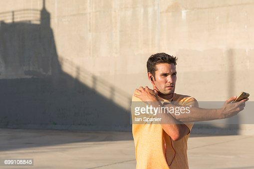 'Male athlete listening to music and stretching, Van Nuys, California, USA'