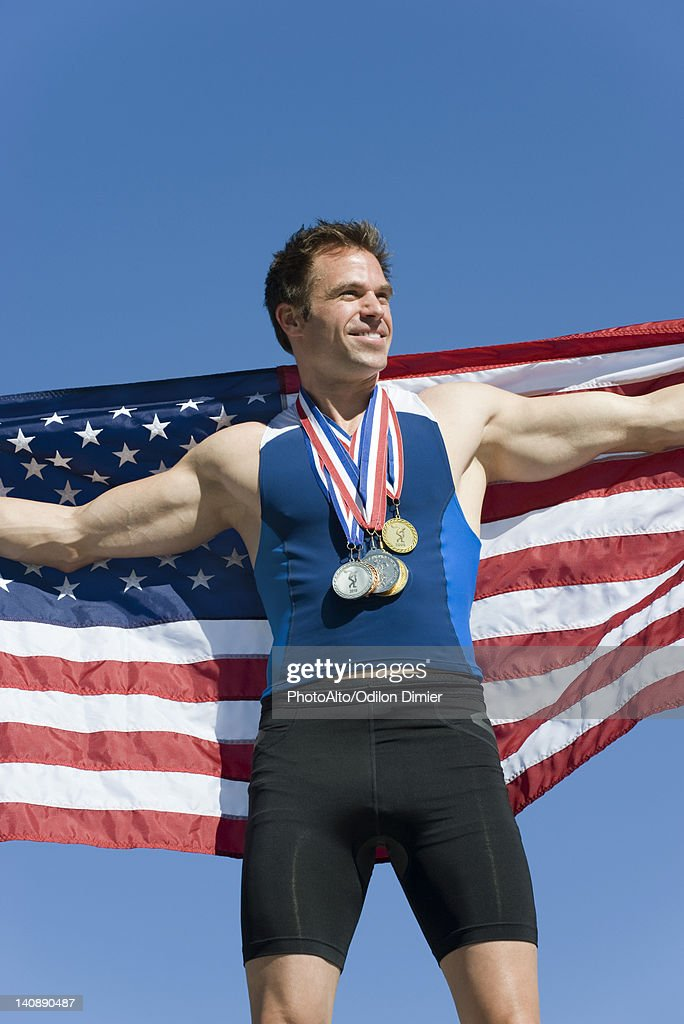 Male athlete on winner's podium, holding up American flag