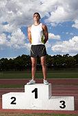 Male athlete on winners podium on track