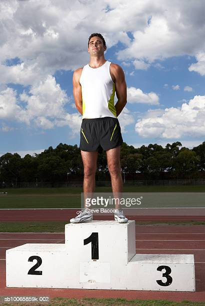 Male athlete on winners podium on track
