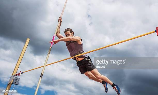 Männliche Athlet performing Hochsprung gegen den Himmel.