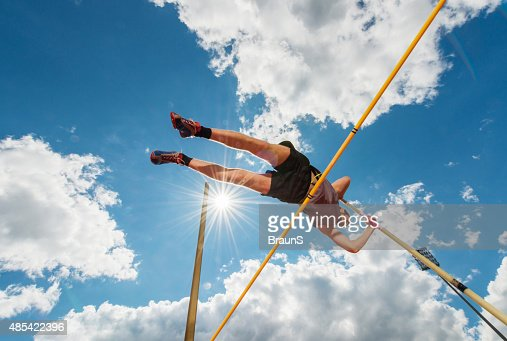 Male athlete performing high jump against the sky.