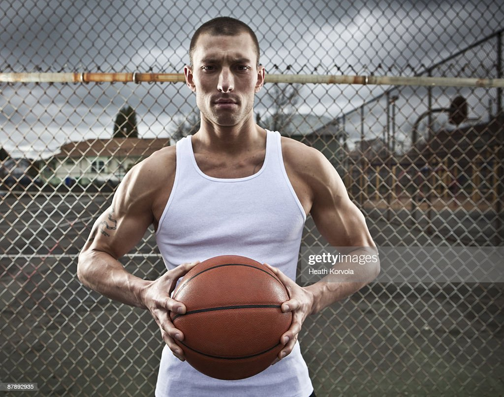 A male athlete poses with a basketball. : Stock Photo