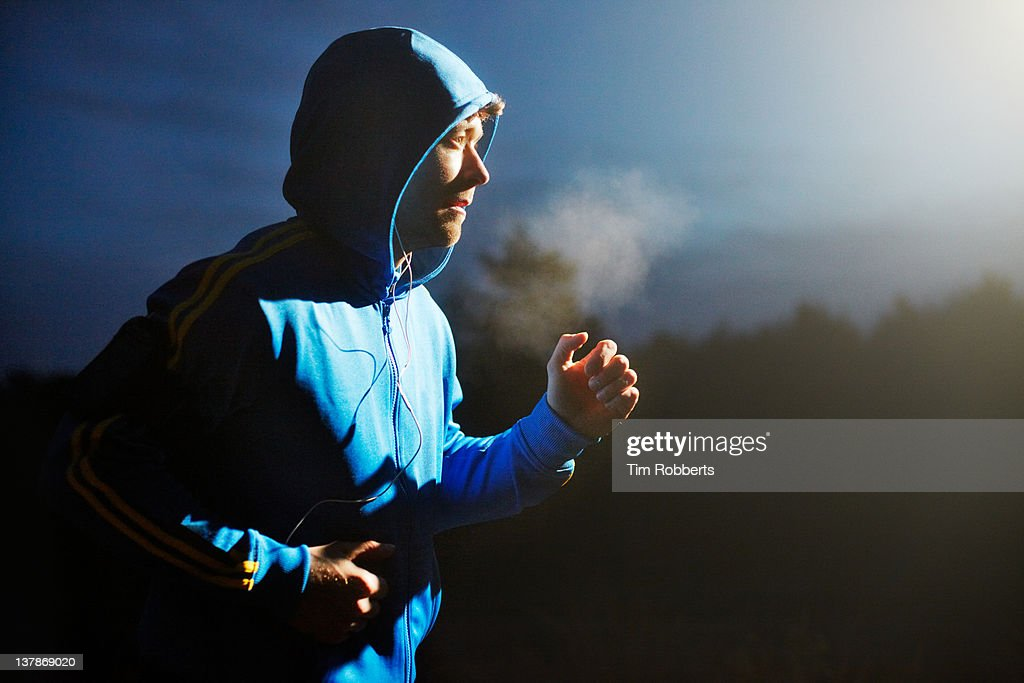 Male athlete running at night with mp3 player. : Stock Photo