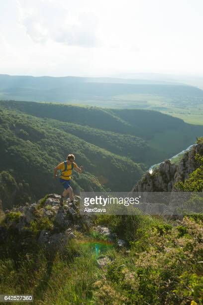 Male athlete running on a mountain trail in summer