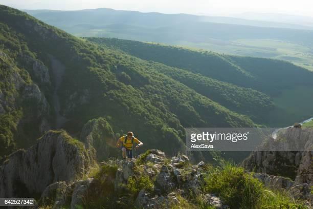 Male athlete running up a steep ridge