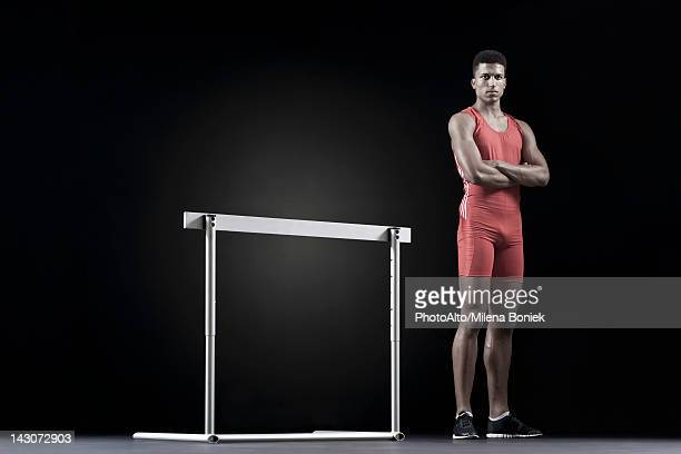 Male athlete standing by hurdle