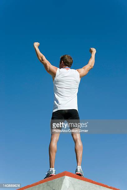 Male athlete standing on winner's podium with arms raised in victory, rear view