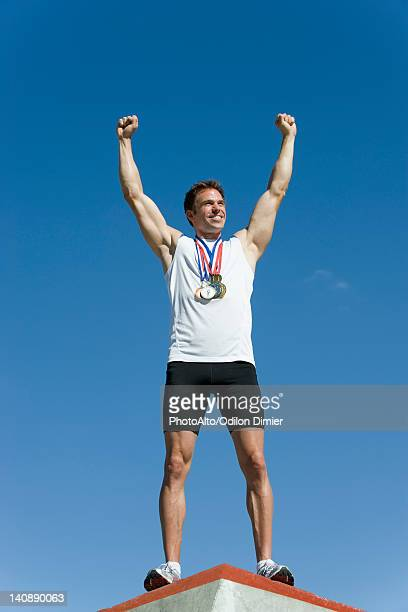 Male athlete standing on winner's podium with arms raised in victory