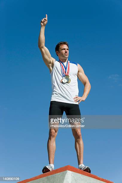 Male athlete standing on winner's podium with hand raised in victory