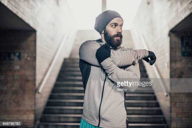 Male athlete stretching his arms in pedestrian subway