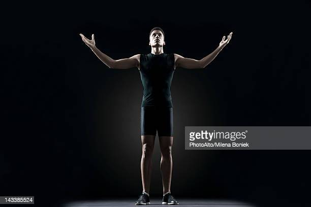Male athlete with arms outstretched, portrait