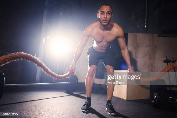 Male athlete working with rope at gym. Mielec, Poland