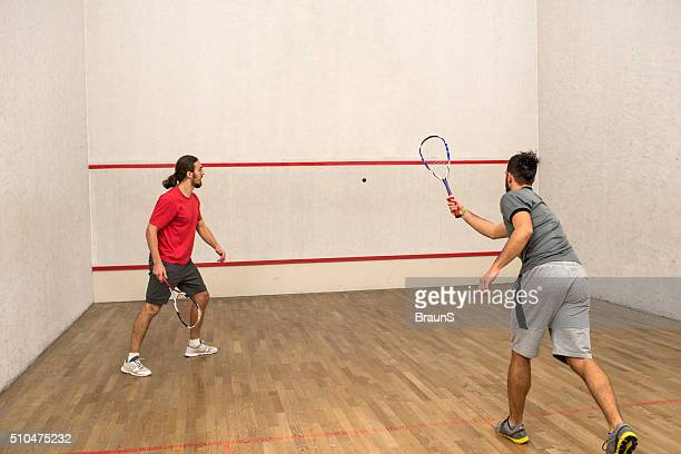 Male athletes exercising racketball on a court.