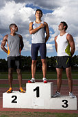 Male athletes looking at winner on podium beside track