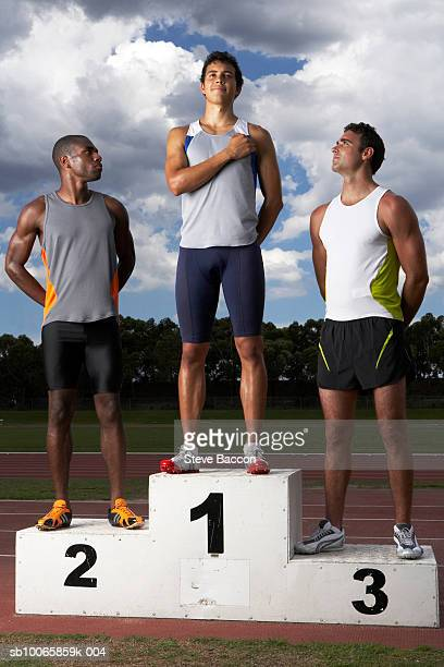 Male athletes looking at winner on podium beside track