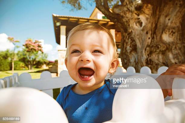 Male baby with open mouth outdoors