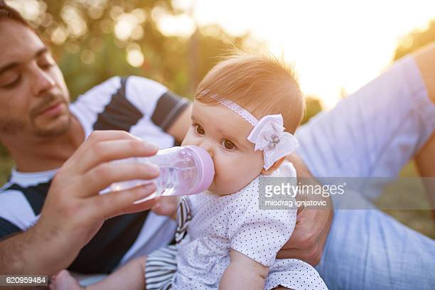 Male babysitter feeding baby girl